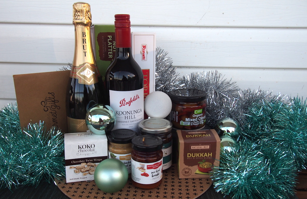 Gourmet Wine Hamper including bottle of red and bottle of bubbly with snacks arranged with tinsel to celebrate Christmas in July. Win Wine Hamper